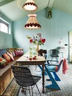 Bohemian dining area with lots of vintage furniture and a cute black and white cat