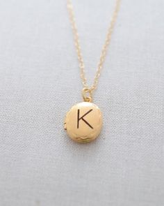 Engraved Oval Gold Locket Necklace by Olive Yew. This small oval 14k gold filled locket necklace has a beautiful diamond cut detail and can be engraved on the front