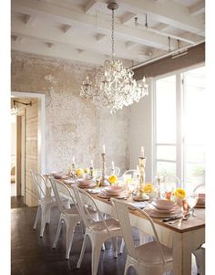 amazing. rustic chic with farmhouse table, rustic walls, glam coffered ceiling, chandy, and TOLIX chairs. perfect blending.