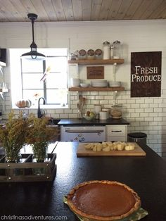 Farmhouse kitchen perfection! This DIY kitchen used to be a PIT! Love the subway tiles, open shelving, wood planked ceiling...