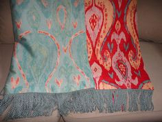 This bold Ikat patterned throw blanket features mesmerizing red, turquoise, gold, and white designs in an upholstery blend fabric. Side two is the fabric reversed, showing more turquoise with a hint of tangerine. Coordinating turquoise aqua bullion fringe on each end pulls the two sides together. The entire throw blanket is breath taking--fabric is substantial, yet soft. If you are looking for a power statement to finish a design job, or just something to perk up your tired decor, this is…
