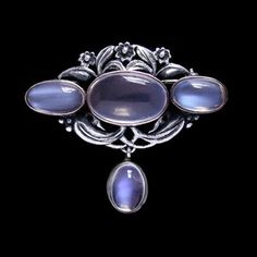 BERNARD INSTONE (Attrib.) An Arts & Crafts silver brooch set with three large moonstones surrounded silver florets and leaves and with a moonstone drop.
