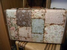 Mod Podge an old suitcase. Looks like scrapbook paper that's been antiqued.