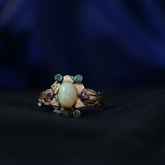 This stunning one of a kind has been handmade in our workshops. It features a central opal, which is surrounded by emeralds and rubelite tourmaline. The ring is made in 18ct gold and oxidized sterling silver and has exquisite hand engraving work on it using floral motifs. Ring size - UK - O 1/2, USA -7 1/2 Ring dimensions - 14mm x 14mm The ring can be resized on request. Alternative Wedding Jewellery, Alternative Engagement Rings, Gemstone Jewelry, Gold Jewelry, Tourmaline Ring, Gold Platinum, Oxidized Sterling Silver, Hand Engraving, Opal
