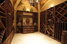 The wine room is stunning with its groin vaulted ceiling and hand painted pastoral scenes, elegant wrought iron chandelier and stair railing, plaster walls, built-in stained wood wine storage compartments and drawers, and travertine flooring.