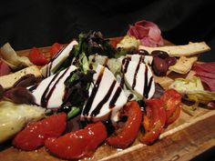 Antipasto Tray at Fat Tomato. Roasted tomatoes, grilled artichokes, prosciutto, pancetta, salami, fresh mozzarella, assorted olives and a balsamic reduction drizzle