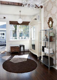 Eteisestä oli ennen sisäänkäynnit kahteen eri asuntoon. Poistamalla kuisti eteiseen saatiin lisätilaa. Koristeellinen vanha kaappi ja Ikean selkeälinjainen metallihylly ovat sulassa sovussa vieretysten.