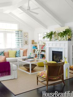 "Bright color and dynamic patterns bring the white living room alive. The Moroccan poufs are a Berman signature. ""I use them a lot in living rooms,"" she says. ""They make great extra seating, especially for kids. And here, they give you a chance to get a shot of leather into the room."" Curtain and blue pillow fabrics are from Duralee's Seaglass Elements print collection. Orange pillows are Meloire Reverse by Quadrille; the yellow pillow is Arcadia Sulphur by Raoul Textiles."