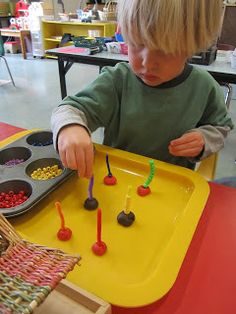 Threading beads onto pipe cleaners stuck in play dough