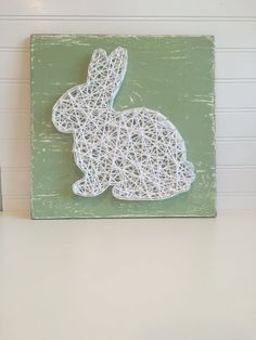 12x12 sage green board with white string art rabbit. by aBitofBeck / Fil tendu: lapin blanc sur planche vert tendre