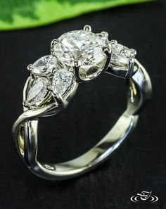 Diamond Twist RingGorgeous diamond center is accented with clusters of pear shaped diamonds secured with twist mounting.