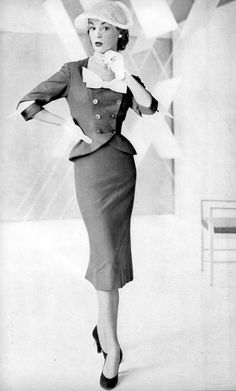 Jean Patchett in fitted suit with short flared jacket by Joseph Halpert, Vogue, April 1, 1951