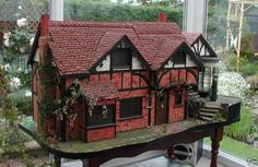 Brick house (jt-don't know anything about this dolls house but wish I did .. it looks interesting - also really like the rounded/bow window at top of the steps - wonder what the window shopper's looking at?)