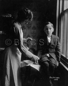 Visiting Nurse takes pulse of young boy diagnosed with typhoid fever, Visiting Nurse Society of Philadelphia, 1919. Image courtesy of the Barbara Bates Center for the Study of the History of Nursing.
