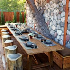 Designer Jamie Durie framed this outdoor dining room by incorporating a large backyard pine tree into a stone wall.