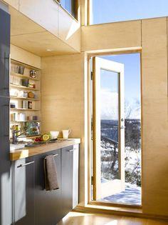 RETT UT: Døren ved kjøkkenet i denne hytta gjør det enkelt å spise frokost ute på trappa i godt vær. Innredning fra Kvik. Veggene er kledd med bjørkefiner.