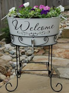 Welcome Tub Planter ... with a little creativity, this container garden has been embellished with vinyl lettering as a warm invitation to guests and planted with colour. Add stencilling to just about any container to add your own creative touch - your family name, street number or house name. | The Micro Garden