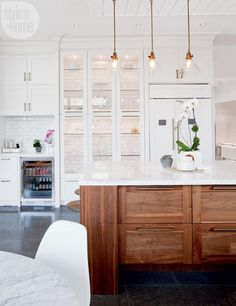 Restaurant-Style Kitchen with floor-to-ceiling tiles, mix of open and closed storage and high-end appliances. A white Shaker-style cabinetry is warmed up with a walnut island and brass hardware statement lighting and fixtures. Cabinets with glass doors allow Tanya to display her favorite serving pieces and special glassware. She had the back of the kitchen cabinets tiled to highlight this focal point of the kitchen. | DesignTanya Krpan, design director for Earls Kitchen + Bar.