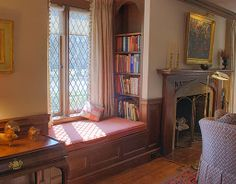 Living room with dark wood wainscoting, built-in bookcases, window seats and Tudor arch fireplace mantle