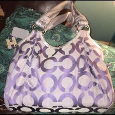 🎉 Authentic Coach Parker Handbag This is an amazing handbag. I love it dearly but it is just hanging on my rack & isn't being used. She needs a new home where she is used frequently! It is in new condition. It has three compartments w/ the middle one being a kisslock closure. ItIt is grey/silver and lilac signature print. This is a large bag. & the pictures really don't do it justice. I also have the matching trifold w/checkbook wallet. please make an offer! For both pieces I will make an…