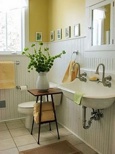 Walls painted in butter yellow with white bead board creates a cozy space in this bath!