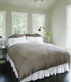 Pale taupe walls juxtapose ebony-walnut stained floors in this blissful bedroom. White framing around the windows are a simple way to pick up the light, while a soft slate duvet cover and a crystal chandelier add a feeling of richness and warmth.   - CountryLiving.com