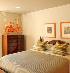 Striped pillows and a favorite orange paint give cohesion to this boy's bedroom. #interior decorating @reduxvirtualdes