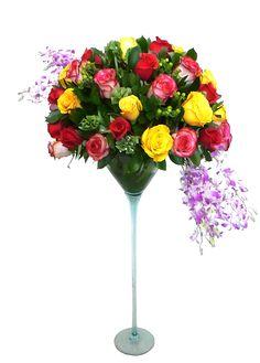 diseño circular en rosas de diversos colores, acompañadas de hypericum verde, follajes, y cascadas en orquidea dendrobium