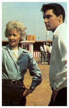 """Barbara Stanwyck and Elvis on the movie set for """"Roustabout"""" - a 1964 American musical feature film starring Elvis Presley as a singer who takes a job working with a struggling carnival. The film was produced by Hal Wallis and directed by John Rich from a screenplay by Anthony Lawrence and Allan Weiss."""