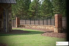 Metal fencing on stone knee-wall between brick columns. #metalfence #fencing