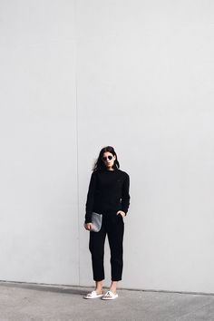 Elisa from www.schwarzersamt.com is wearing an allblack look with CALVIN KLEIN slipper, H&M glasses, an AMERICAN VINTAGE clutch, ASOS TALL pants and an CALVIN KLEIN sweater. minimal, monochrome, black blogger streetstyle look