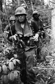 A file of soldiers on a routine jungle patrol. Most soldiers wore towels around their necks, like this one did, to help combat sweat in the jungle heat. Names, date, and location unknown.