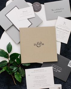"The invitation suite created by @chereeberrypaper for Danielle and Shaun's Atlanta wedding encapsulated what I'm calling ""New Traditional Style,"" from the mix of neutrals to the typography to the packaging. All components were held within a taupe linen wrapped booklet stamped with the couple's initials in graphite foil. Each booklet was encased in a light grey inner envelope folder and mailed off in a white calligraphed box. Photo by @kateheadley. @brides. #BridesRealWeddings…"