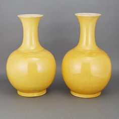 Pair of Chinese Yellow Glazed Porcelain Vases Guangxu Mark and of the Period. Each globular body rising to a tall neck flared at the rim, covered overall in a bright even yellow glaze, the interior of the neck glazed in white with a fine craquelure. Height 15 1/4 inches.