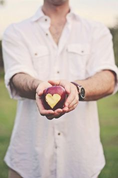 Fiance holding red apple with heart bit out by Stephie Hicks Photography | Done Brilliantly