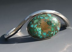 a beautiful solid sterling silver bracelet with a large turquoise set stone by craig moore