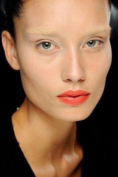 Runway makeup, coral orange lips, bleached eyebrows. Backstage at Rick Owens, RTW Spring / Summer 2012. Photo: Luca Cannonieri / Go Runway