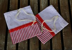Set of 2 cotton red and white gift bags with red laces.