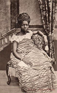 Image produced between 1900 and 1910 by the photographer F.W.H Arkhurst in Grand Bassam, Ivory Coast. His studio photographs capture the then fashionable style of women's dress along the African coast from the Niger Delta to the Ivory Coast as families grew prosperous from trading opportunities in the expanding colonial economies. Hair was swept high and adorned with gold jewelery or wrapped in cloth. Tailored dress of imported cotton prints, often with a shawl or wrap of locally woven…