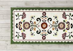 Kleurrijk tapijtje in de slaapkamer waar natuurlijk hout en simpele lichte kleuren domineren