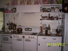 Another view of the same kitchen. All this was added to match and coordinate with original cabinets.  Vintage store is a workhorse and a dream to cook on.  Large center area is a dream when canning. Bulky cooking utensils displayed in silver champagne buckets.