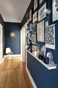 Blue walls in hallway with retro 'Pistillo' wall lamp & wall gallery on the right