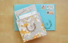 DIY Einladung für Hochzeit: blauer Kartenumschlag mit Postmarken, Stoffumschlaf aus Musterpapier in Gelb, Weiß und Grau