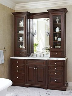 This traditional bathroom vanity has the look of breakfront cabinetry with upper cabinets that sit atop the counter to frame the bathroom sink. Glass doors allow you to display collectibles, while other bathroom essentials are strategically tucked away. A pair of crystal sconces mounted on the mirror contribute drama and an extra touch of sparkle.