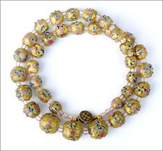 Antique gold washed Venetian Wedding Cake bead necklace in excellent condition. The beads graduate from 13 mm to 7 mm in diameter with tiny very pale opalescent pink spacer beads