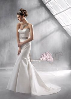 Ivory Duchess silk satin trumpet bridal gown accented with jeweled buckle on platinum tie ribbon at natural waist, chapel train.