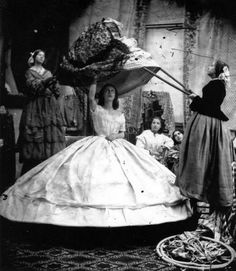 1890 -----  A woman in crinoline requires the help of long poles to put on her dress. c 1890
