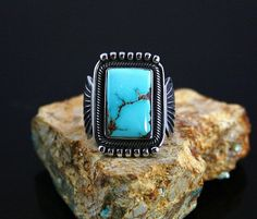 Terry Martinez RARE Gem Grade Aztec Turquoise Ring | eBay  This amazing one of a kind ring was created by award winning Navajo artist, Terry Martinez. The piece features rare gem grade natural Aztec turquoise from Nevada with an elegant sky blue hue and dark reddish-brown matrix. Beautiful silverwork compliments the stone with hand twisted wire encircling the bezel and sterling silver droplets in the upper and lower portions of the ring face.  $450