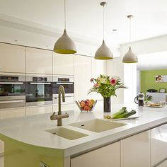 This fresh white and green kitchen looks great with the pops of colour on the insides of the pendant lights and the adjacent study nook area.  It also has a Corian worktop with a moulded bowl which works well with the modern look of this space.