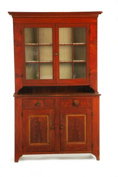 "Garth's Auctions, Inc. - Auctioneers & Appraisers   Sold for $11,400 DECORATED STEPBACK CUPBOARD.   Pennsylvania, early 19th century, pine. Two-piece cupboard: the upper section with two six-pane doors and interior shelves with plate grooves and spoon slots, the lower section with two drawers over two doors and cutout bracket feet. Retains its original red paint with black graining and yellow trim on the lower doors to mimic raised panels. 88""h. 55""w. 20""d."